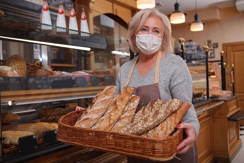 Woman working in bakery holding a basket of bread loaves