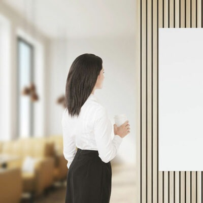 Woman staring at blank white panel that is hanging on a wall